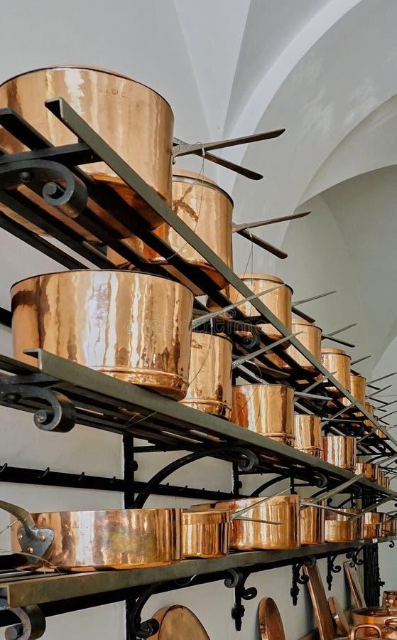 Drie die planken met grote koper kokende potten worden gevuld royalty-vrije stock afbeelding