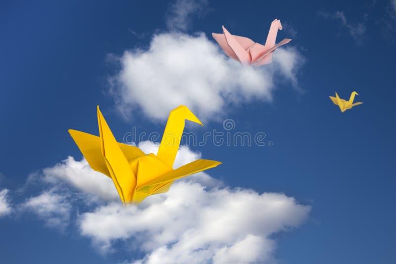 Drie document kranen die boven wolken vliegen. stock fotografie
