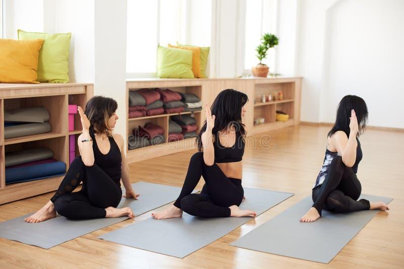 Drie donkerbruine vrouwen die tijd hebben bij yogaklassen, uitoefenend flexibiliteit in Halve Lord van de yogazitting van de viss royalty-vrije stock afbeelding