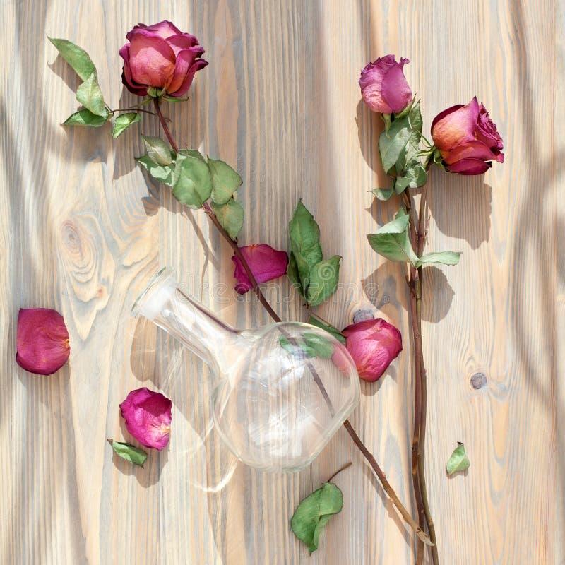 Drie droge roze rozen, verspreide bloembloemblaadjes, groene bladeren, glasvaas op houten hoogste mening als achtergrond dicht om royalty-vrije stock fotografie