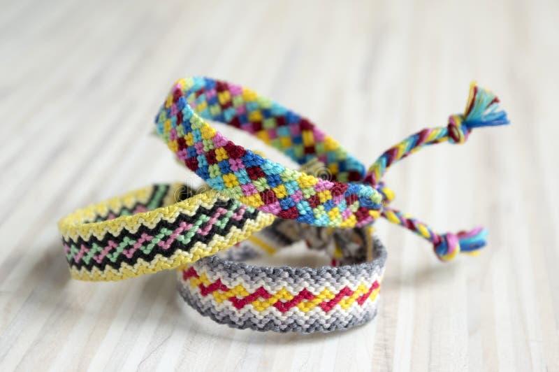 Drie eenvoudige met de hand gemaakte eigengemaakte natuurlijke geweven armbanden van vriendschap op witte houten lijst royalty-vrije stock foto's