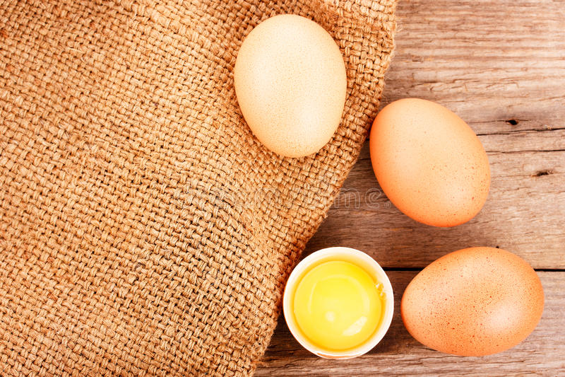 Drie eieren op een houten raad en jutezak stock afbeelding