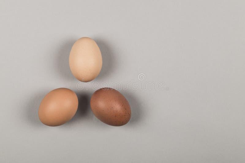 Drie eieren van verschillende schaduwen in een driehoekspatroon royalty-vrije stock afbeelding