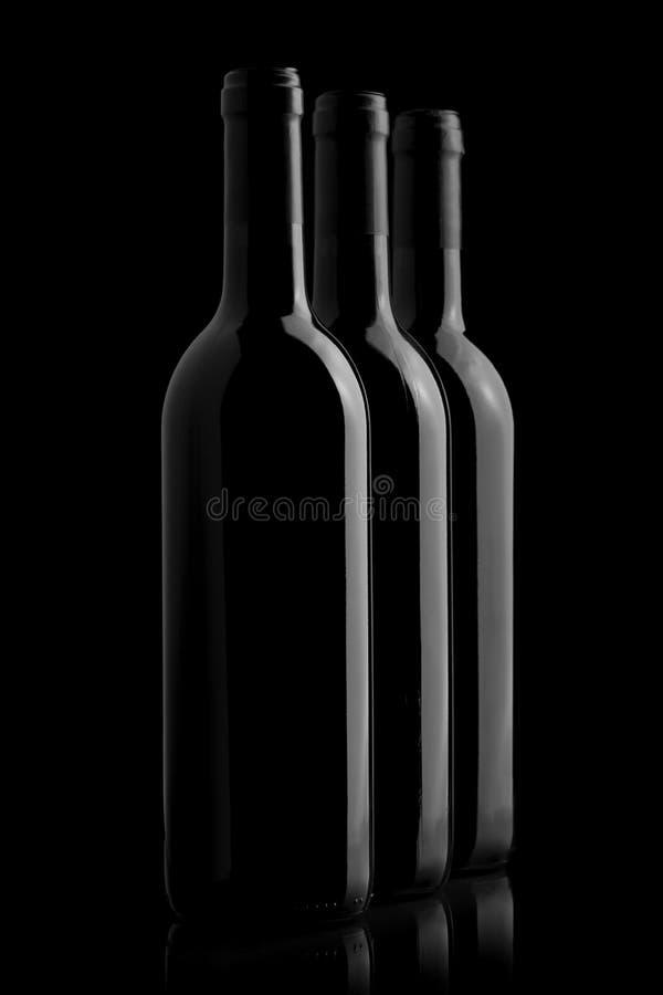 Drie elegante wijnflessen op zwarte achtergrond royalty-vrije stock foto's