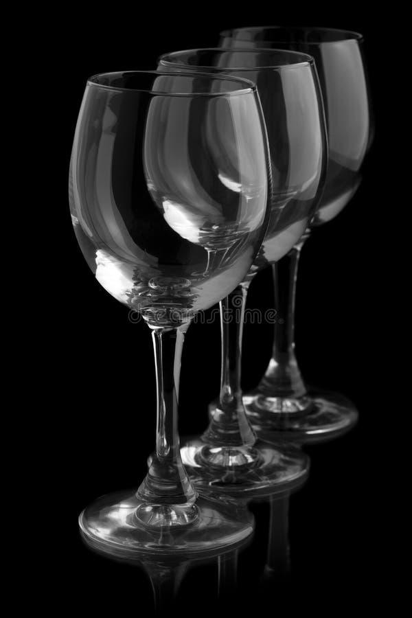 Drie elegante wijnglazen op zwarte achtergrond stock afbeeldingen