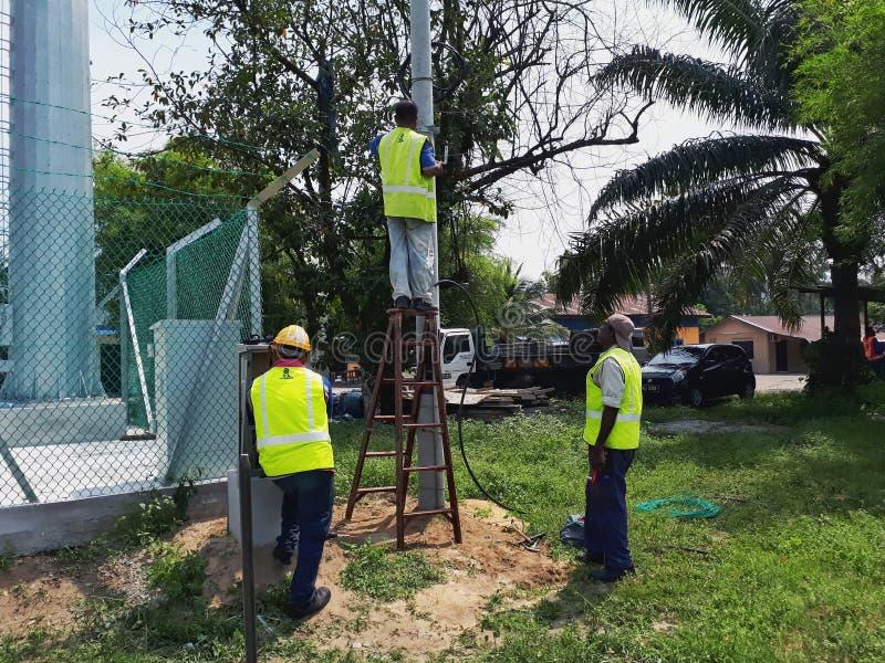 Drie elektriciens installeren de luchtkabel in drie stadia van de vier kernmacht op gesponnen beton stock foto's