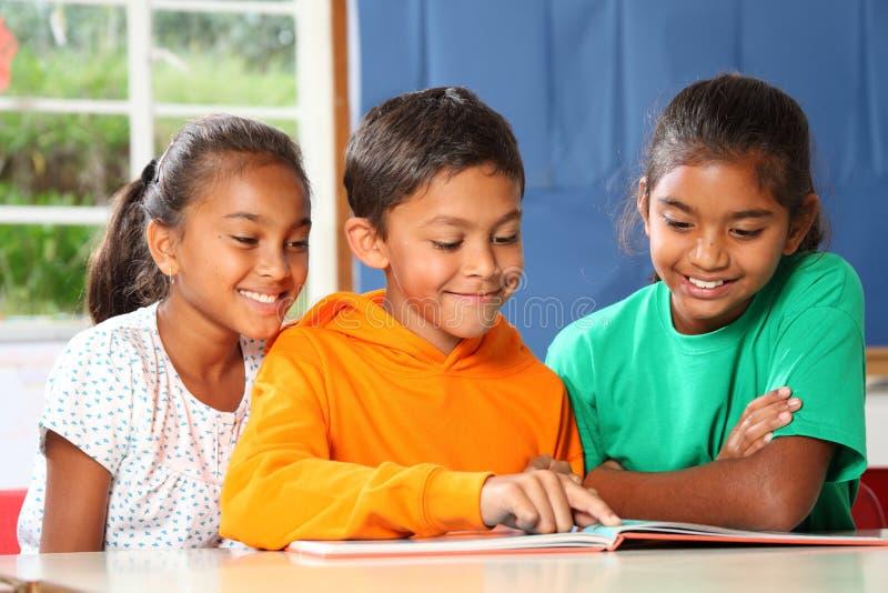 Drie en lage schoolkinderen die lezen leren stock afbeeldingen