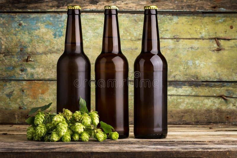 Drie flessen bier op houten achtergrond stock foto