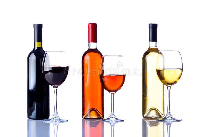 Drie flessen en glazen wijn stock foto's