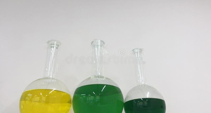 Drie flessen met gekleurde vloeistoffen stock foto