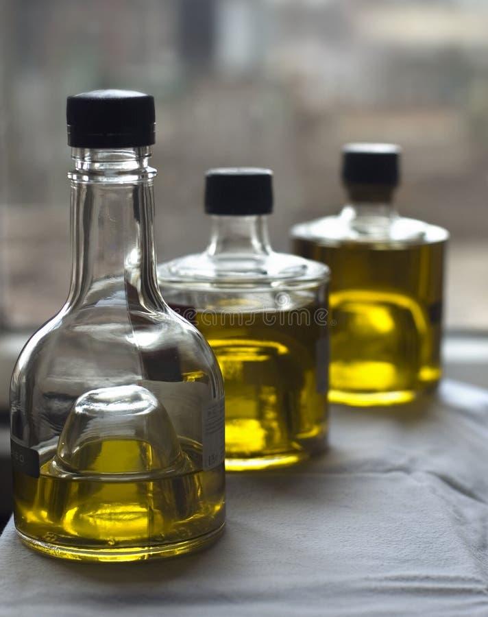 Drie flessen olijfolie stock afbeeldingen