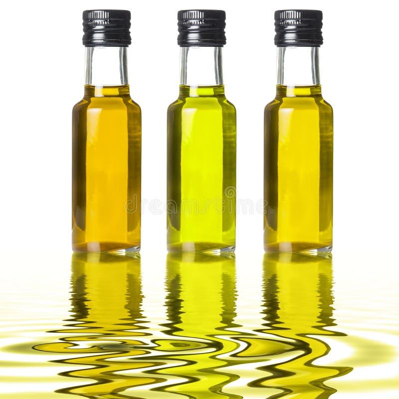 Drie flessen verschillende olijfolie op vloeibare bezinningen royalty-vrije stock afbeeldingen