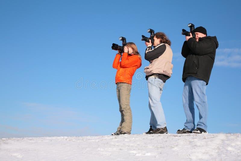 Drie fotografen op sneeuwheuvel stock foto's