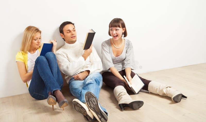 Drie geamuseerde vrienden met boeken stock afbeeldingen
