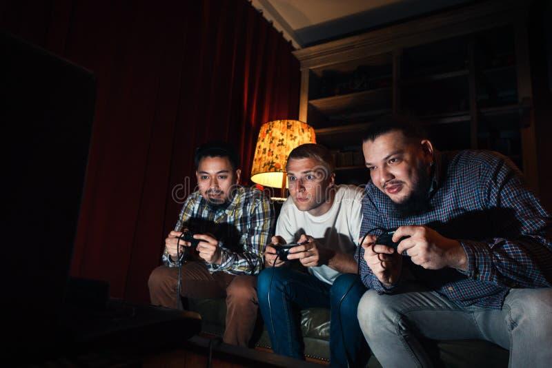 Drie geconcentreerd jong het huisvideospelletje van het kerelspel royalty-vrije stock foto