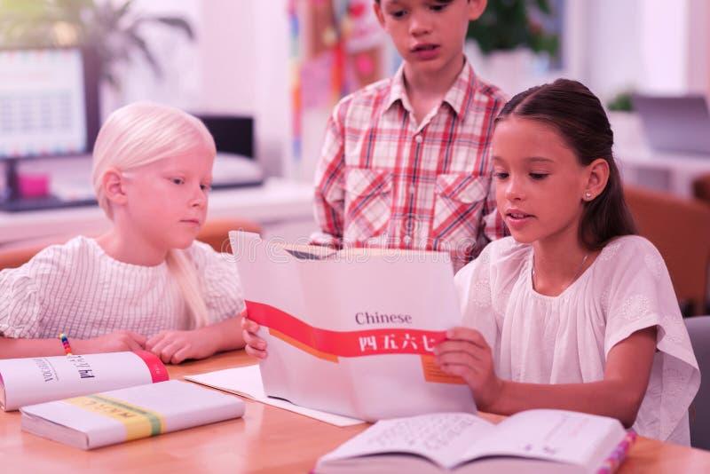 Drie geconcentreerde kinderen die Chinees leren op school royalty-vrije stock foto