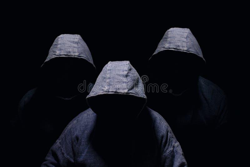 Drie geheimzinnig mensensilhouet met verdonkerd gezicht, geen zichtbaar gezicht, in blauwe hoodies stock fotografie