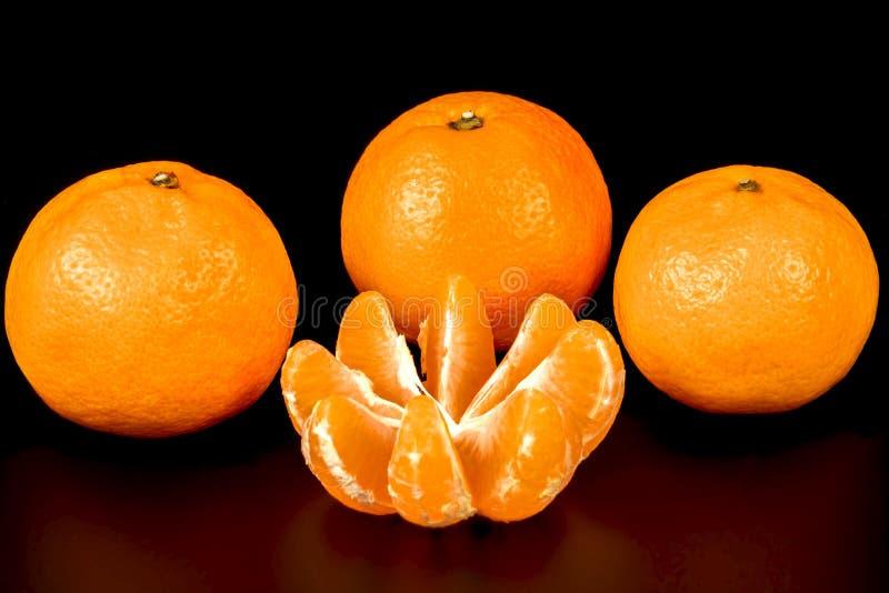Drie gehele die mandarijnen en één op een zwarte worden ontruimd royalty-vrije stock afbeeldingen