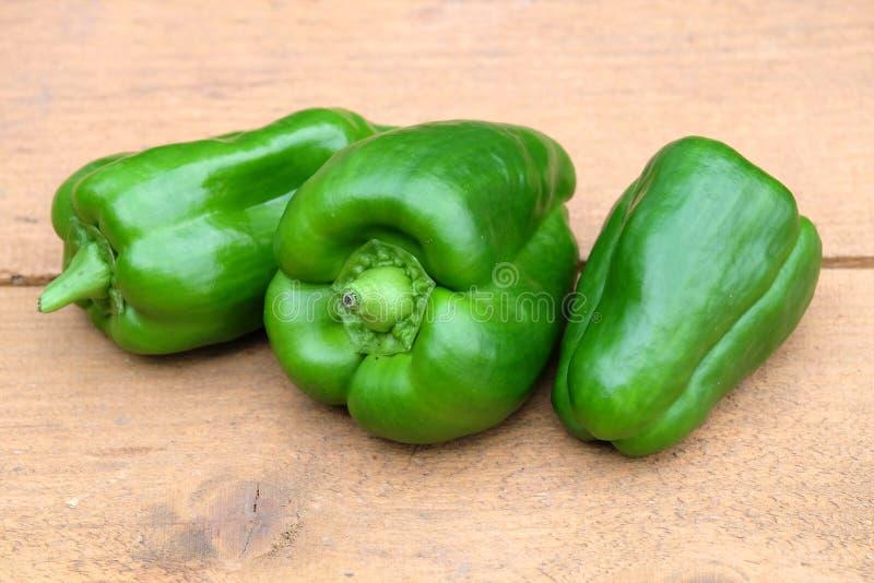 Drie gehele groene rijpe die groene paprika's op bruine houten oppervlakteclose-up worden geïsoleerd stock foto