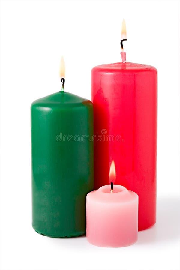 Drie gekleurde brandende kaarsen. Geïsoleerde royalty-vrije stock afbeeldingen