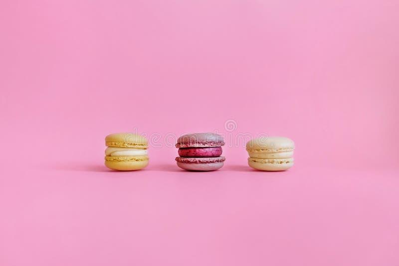 Drie gekleurde makarons op een purpere achtergrond stock afbeelding