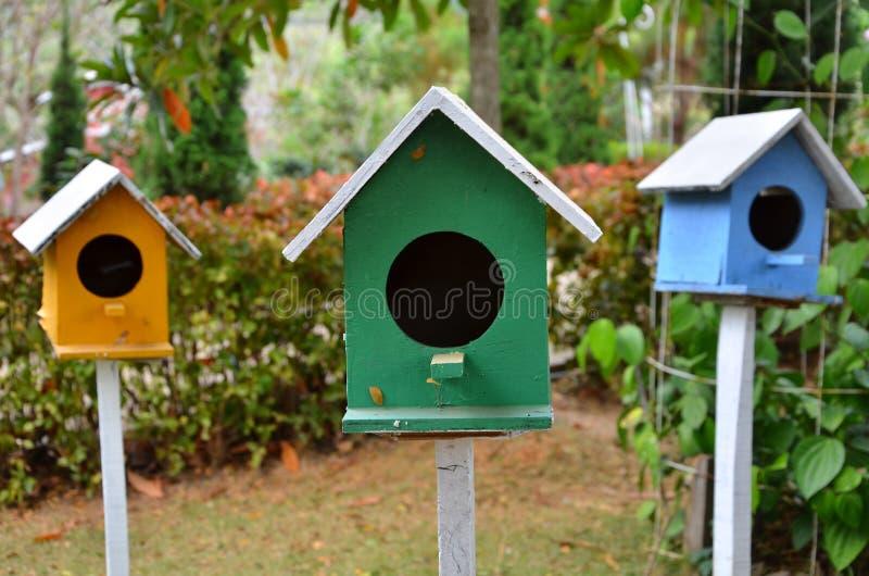 Drie gekleurde vogelhuizen stock afbeelding