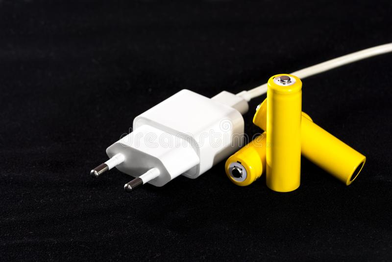 Drie gele batterijen en batterijlader stoppen close-up op een donkere zwarte vage achtergrond electrics Batterijmacht Accumulato stock afbeeldingen