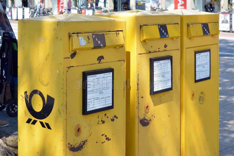 Drie gele officiële openbare postdozen in een slechte staat op straat royalty-vrije stock afbeelding