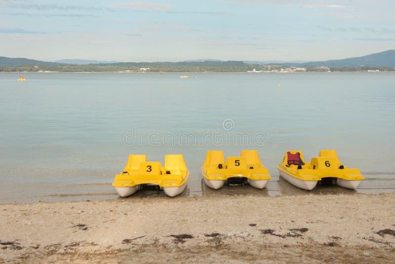 Drie gele pedaalboten voor huur stock foto's