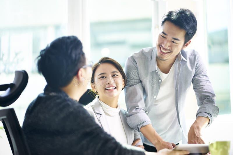 Drie gelukkige Aziatische teammates die zaken in bureau bespreken royalty-vrije stock foto
