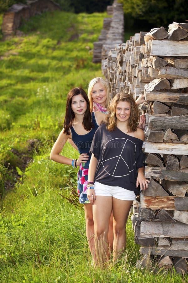 Drie gelukkige en glimlachende tieners stock foto's