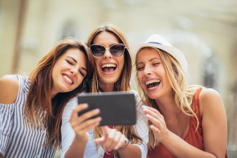 Drie gelukkige glimlachende vrouwelijke vrienden die een tabletcomputer delen aangezien zij zich dicht bij elkaar bevinden bekijk stock fotografie