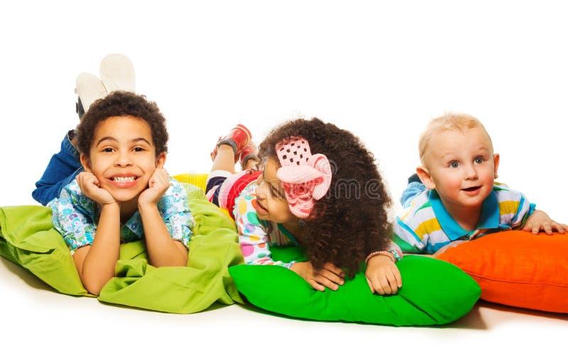 Drie gelukkige jonge geitjes op de hoofdkussens royalty-vrije stock foto