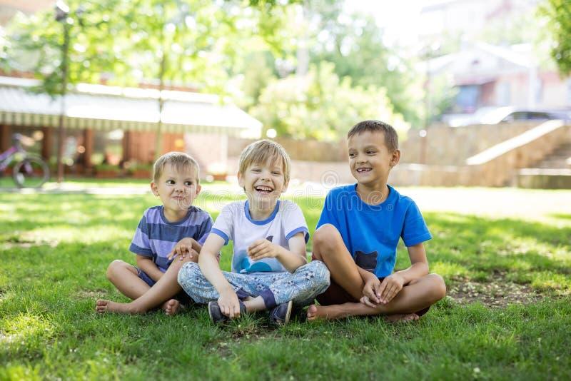 Drie gelukkige jonge jongens in de zomerpark royalty-vrije stock afbeelding