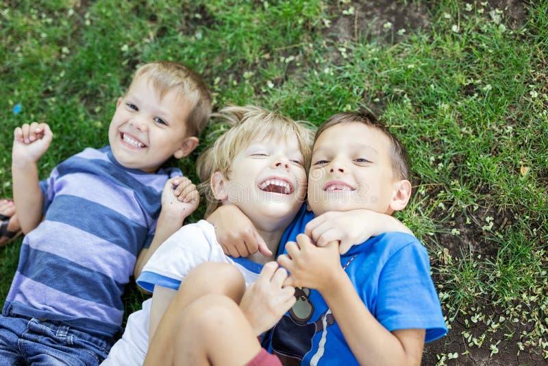 Drie gelukkige jonge jongens die op gras in de zomerpark liggen royalty-vrije stock foto