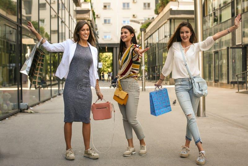 Drie gelukkige jonge vrouwen na het winkelen stelt op straat stock foto's