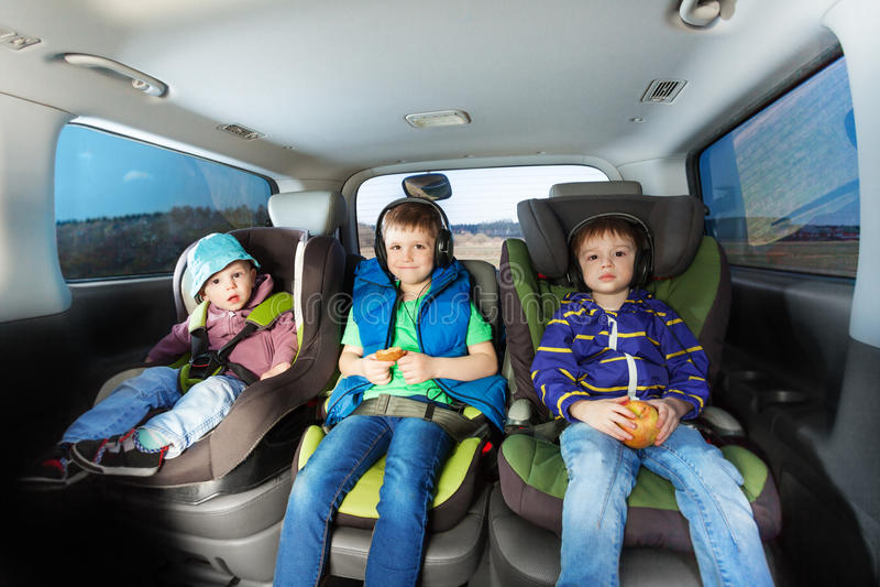 Drie gelukkige jongens die in de zetels van de veiligheidsauto zitten royalty-vrije stock fotografie