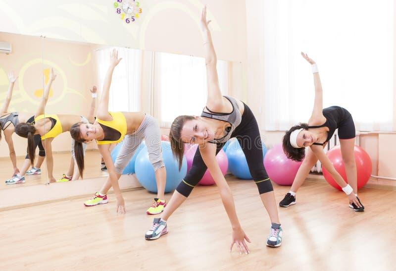 Drie Gelukkige Kaukasische Vrouwelijke Atleten in Goede Pasvorm die Uitrekkende Oefeningen hebben stock afbeelding