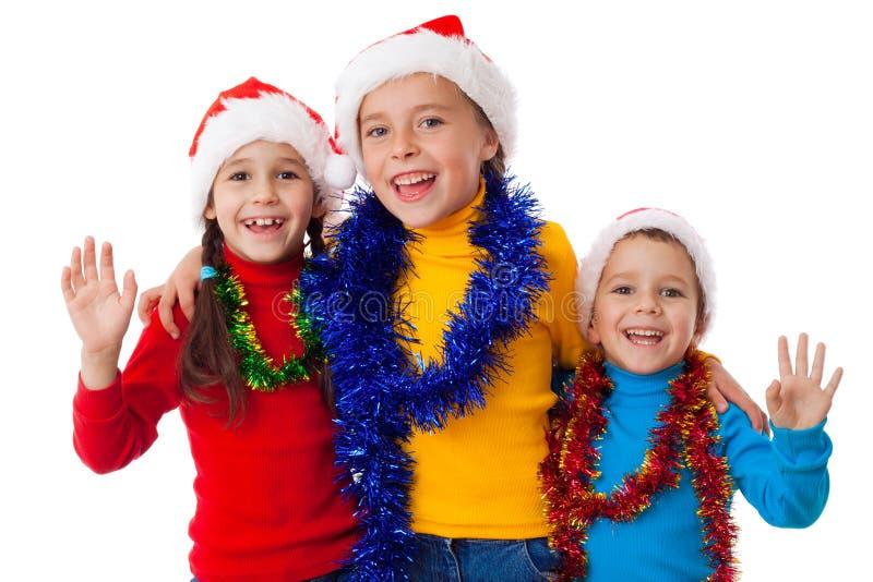 Drie gelukkige kinderen in de hoeden van de Kerstman royalty-vrije stock afbeeldingen