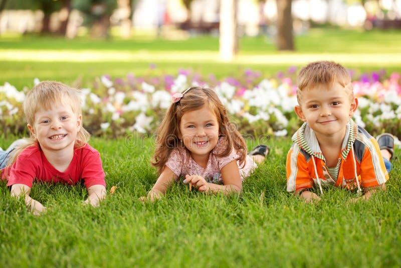 Drie gelukkige kinderen die op het gras liggen royalty-vrije stock foto