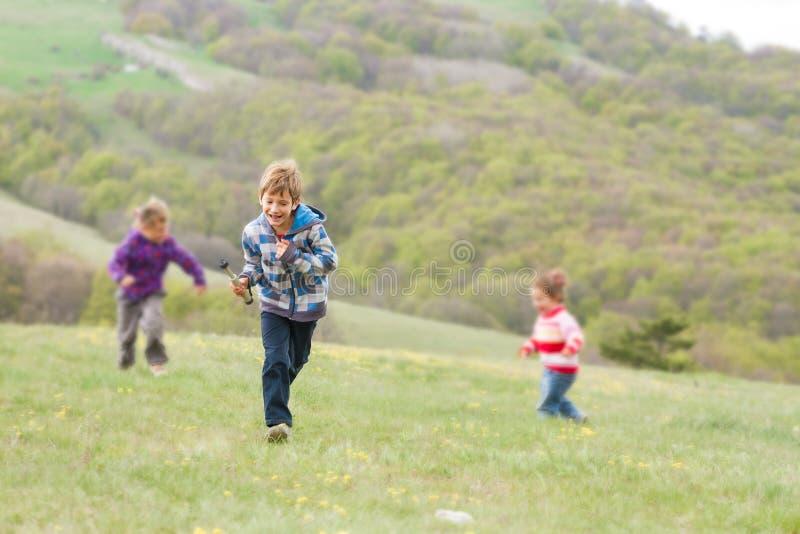 Drie gelukkige kinderen die pret op natuurlijke achtergrond hebben stock afbeeldingen
