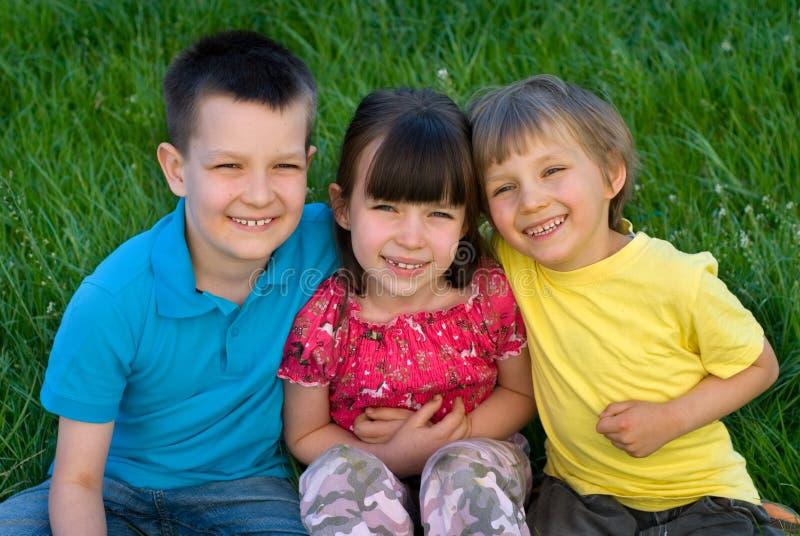 Drie gelukkige kinderen in gras royalty-vrije stock foto's