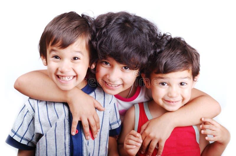 Drie gelukkige kinderen isoleerden: liefde, zorg, omhelzing, stock foto's