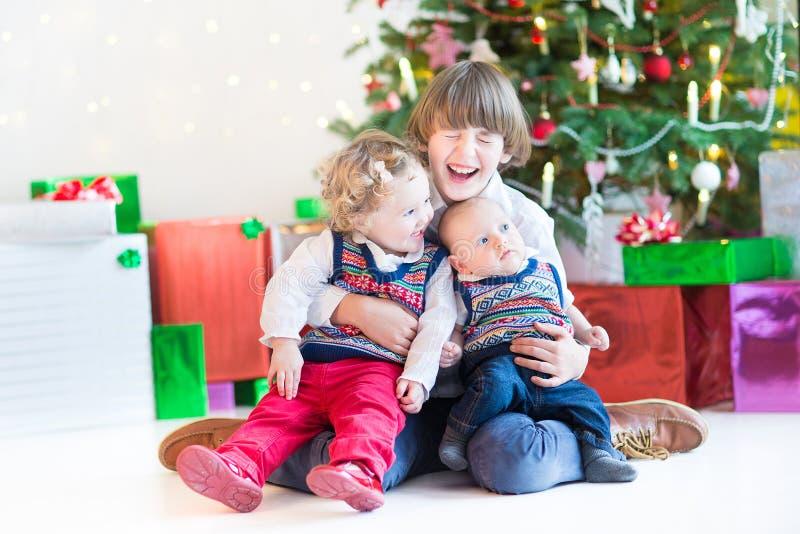 Drie gelukkige kinderen - tienerjongen, peutermeisje en hun pasgeboren babybroer die - samen onder Kerstboom spelen royalty-vrije stock afbeelding
