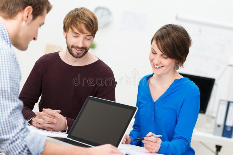 Drie gelukkige medewerkers in een vergadering royalty-vrije stock foto