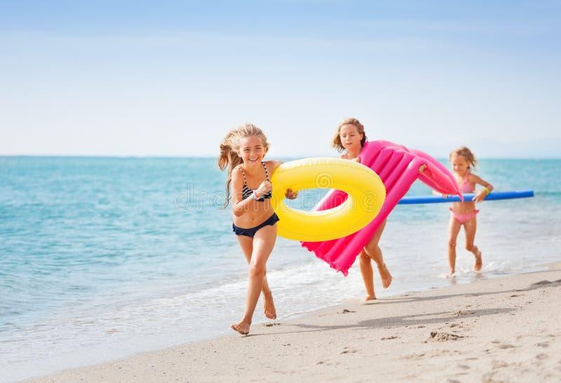 Drie gelukkige meisjes die pret hebben die bij het strand lopen royalty-vrije stock afbeelding