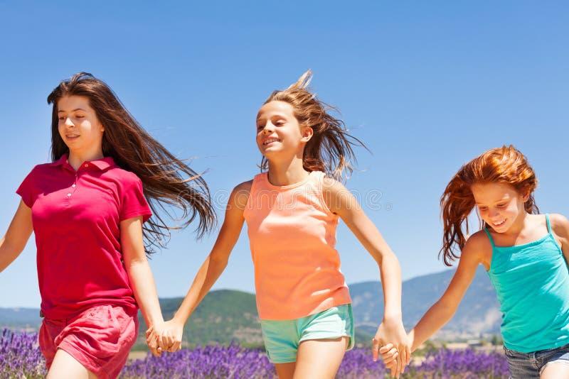 Drie gelukkige meisjes die samen in openlucht lopen royalty-vrije stock afbeeldingen