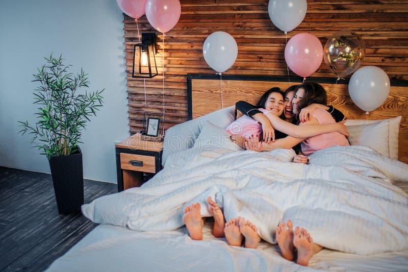 Drie gelukkige onder witte deken liggen samen en modellen die omhelzen Zij glimlachen De meisjes dragen pyjama's Baloons is bij b royalty-vrije stock afbeeldingen