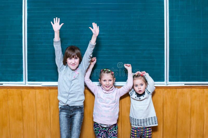 Drie gelukkige schoolmeisjes bij het bord stock afbeeldingen