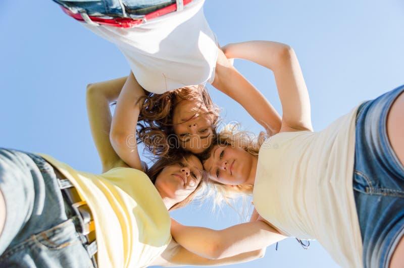Drie gelukkige tienermeisjes die kijken onderaan outdoots royalty-vrije stock foto